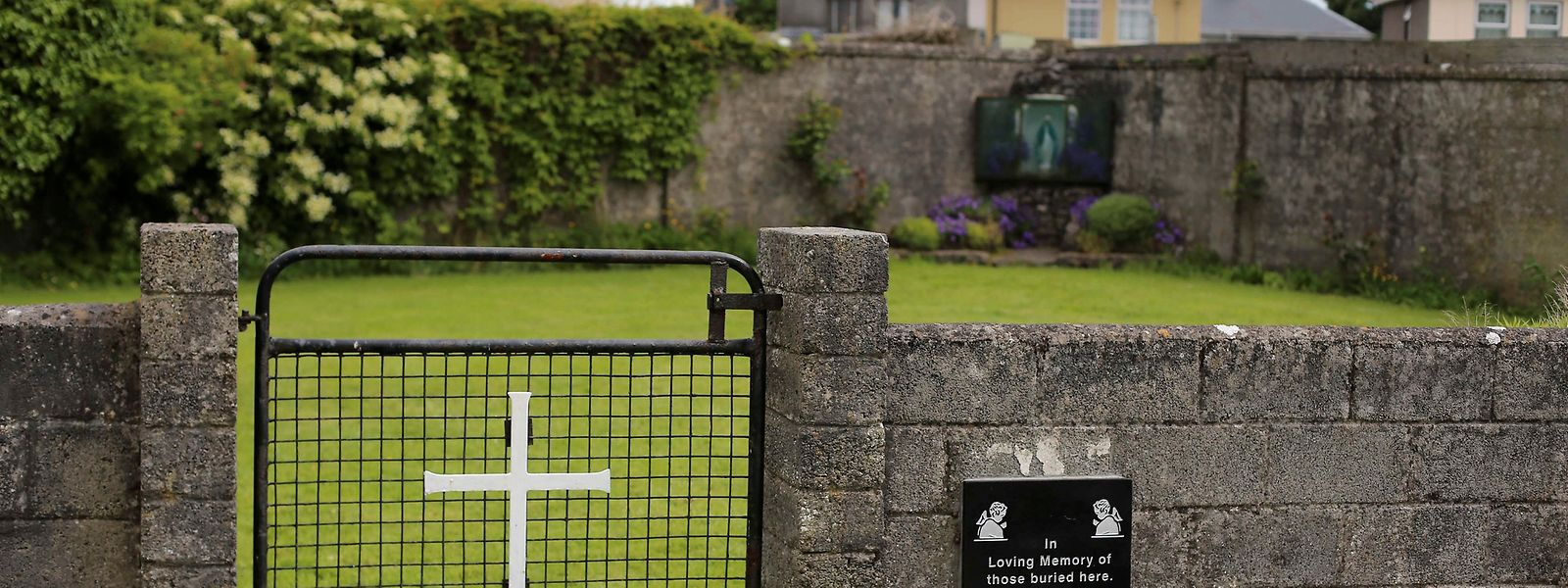Unter dieser Grünfläche fanden die Ermittler das Massengrab, vermutlich aus dem Zeitraum 1925 bis 1961. Die inoffizielle Gedenkplatte rechts im Bild stammt von 2014.