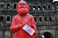 This picture taken on April, 10, 2018 in Trier, southwestern Germany, shows a red figure of German philosopher Karl Marx with a Zero-Euro-bank note realeased on the occasion of Marx's bicentenary. On May 5, 2018 is the 200th anniversary of Marx's birth. / AFP PHOTO / dpa / Harald Tittel / Germany OUT
