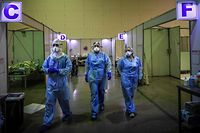 TOPSHOT - Healthcare workers wearing protective gear prepare to attend  patients at the Portimao Arena sports pavilion converted in a field hospital for Covid-19 patients at Portimao, in the Algarve region, on February 9, 2021. (Photo by PATRICIA DE MELO MOREIRA / AFP)