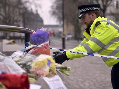 A police officer reaches out to floral tributes in Westminster the day after an attack, in London, Britain March 23, 2017.   REUTERS/Hannah McKay