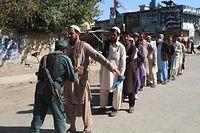 Ein Polizist durchsucht Wähler, die vor dem Wahlbüro anstehen.