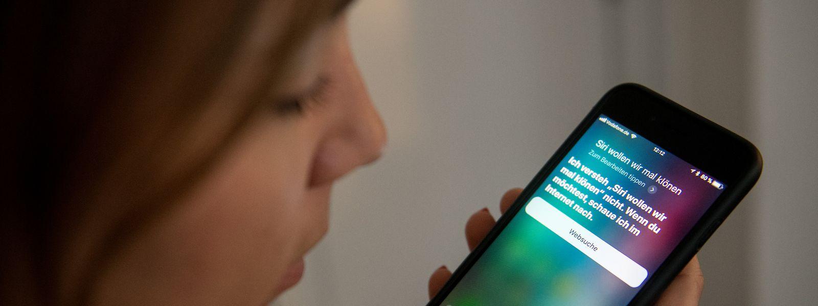 Eine junge Frau bedient auf einem iPhone die Spracherkennung des Apple-Programms Siri.