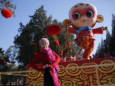 A woman poses in front of a monkey-shaped installation set up for celebrating the upcoming Chinese Lunar New Year of the Monkey ahead of the temple fair in Ditan Park, also known as the Temple of Earth, in Beijing, China, February 5, 2016.REUTERS/Kim Kyung-Hoon