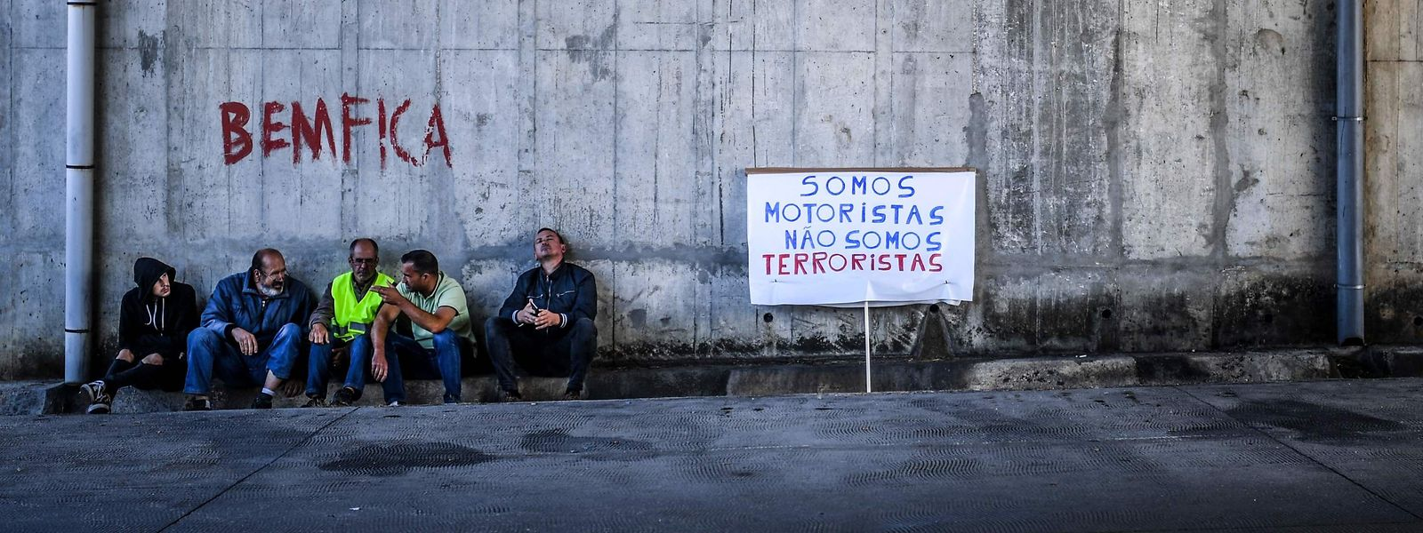 Des grévistes portugais, à côté d'une affiche indiquant «Nous sommes chauffeurs, pas des terroristes».