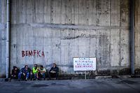 "TOPSHOT - Picketers sit next to a placard reading ""We are drivers not terrorists"" at CLC (Fuel Logistics Company) during the first day of a fuel-tanker drivers' strike in Aveiras de Cima on August 12, 2019. - Portuguese police escorted fuel trucks today to supply petrol stations at the start of a tanker drivers' strike, an AFP reporter said. (Photo by PATRICIA DE MELO MOREIRA / AFP)"