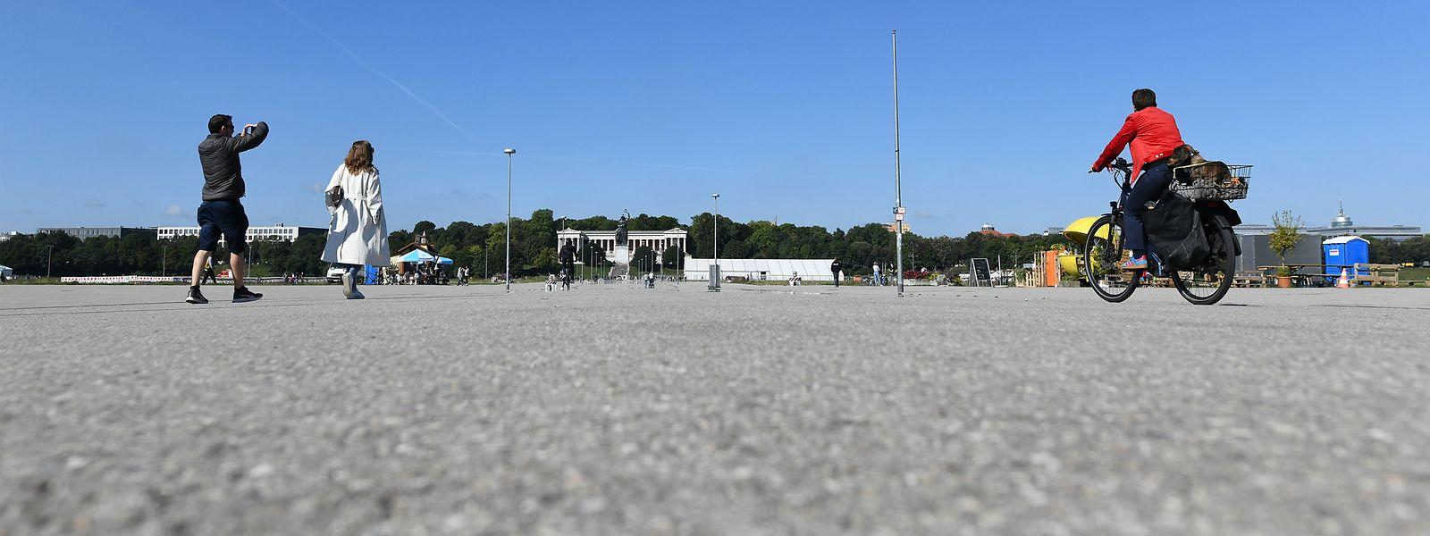 Kalter Beton statt Volksfestatmosphäre: Touristen und Einheimische gehen am Samstag über die leere Theresienwiese.