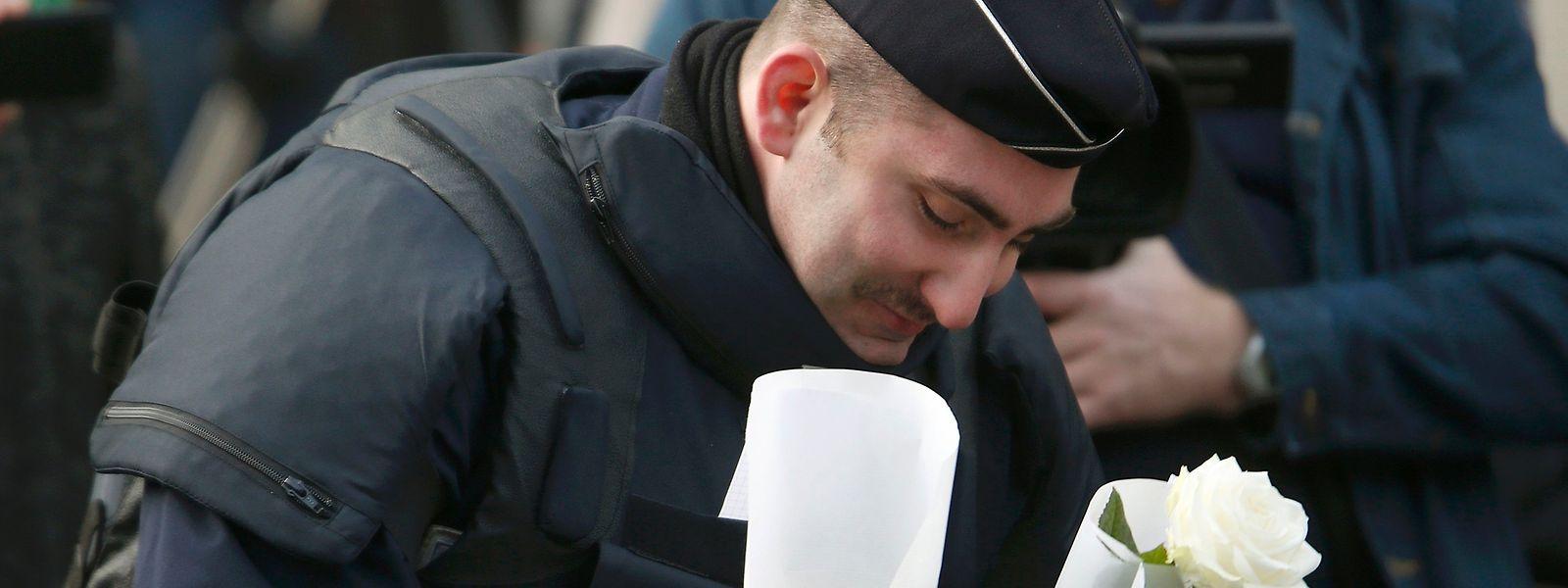 Un policier dépose des fleurs devant le Bataclan, célèbre salle de spectacle parisienne.