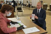 TOPSHOT - Russian President Vladimir Putin shows his passport to a member of a local electoral commission as he arrives to cast his ballot in a nationwide vote on constitutional reforms at a polling station in Moscow on July 1, 2020. (Photo by Alexei Druzhinin / SPUTNIK / AFP)
