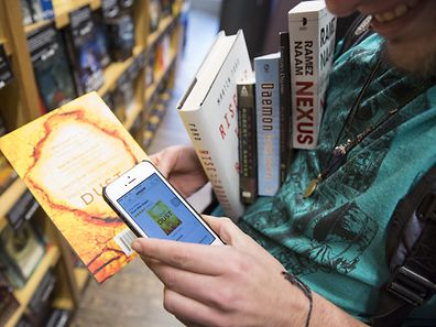 Aidan Devlon, 32, of Seattle, looks up a book on the Amazon smartphone app as he shops in the new Amazon Books store at University Village in Seattle, Washington.