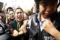 ARCHIV - 07.07.2009, China, Ürümqi: Eine Angehörige der uigurischen Minderheit in China versucht einen Polizisten zu packen, während einer Demonstration in Ürümqi in der Unruheregion Xinjiang in Nordwestchina. Foto: Oliver Weiken/dpa +++ dpa-Bildfunk +++