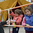 Eine Frau reicht Flüchtlingskindern in München eine Dose mit Bonbons.