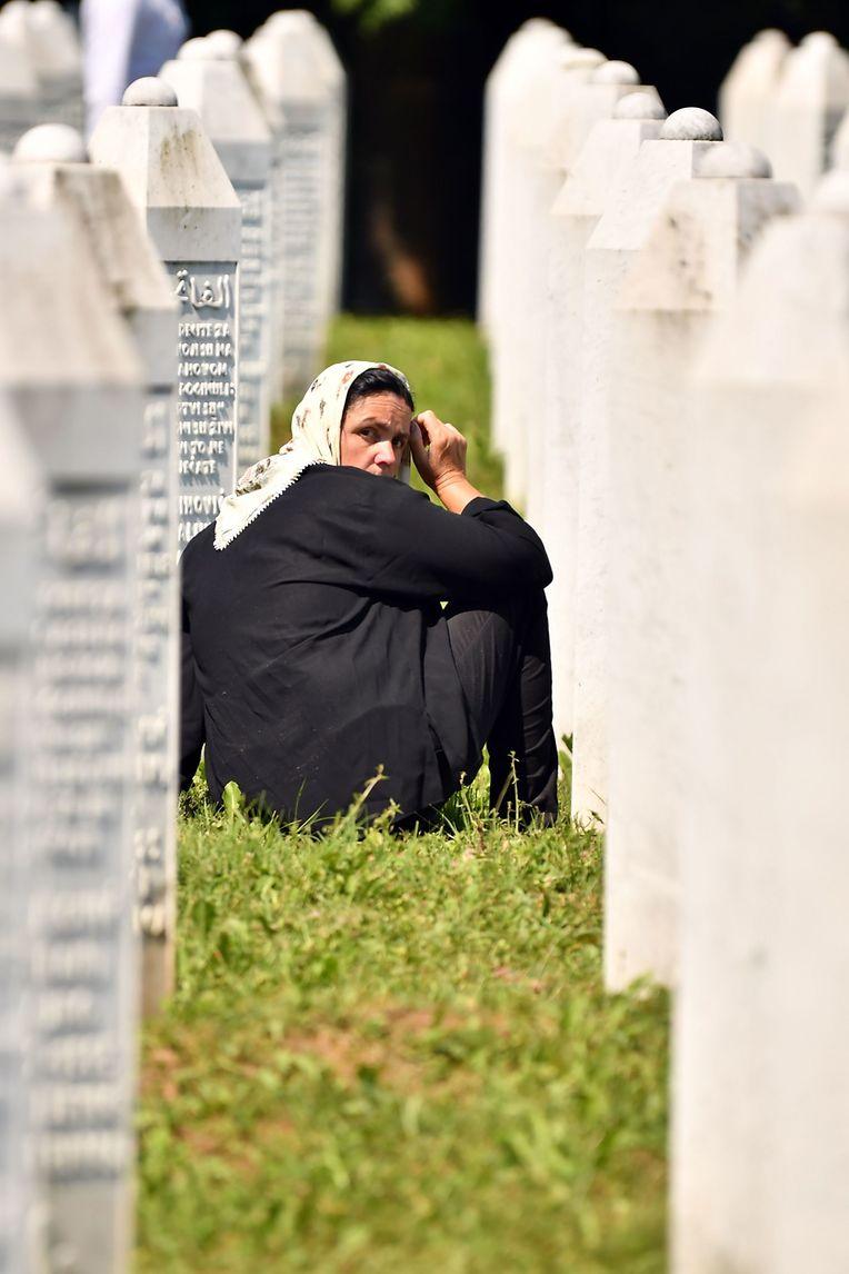 Eine bosnisch-muslimische Frau, die das Massaker von Srebrenica 1995 überlebt hat, sitzt am Samstag auf dem Potocari-Gedenkfriedhof vor den Grabsteinen ihrer Verwandten.