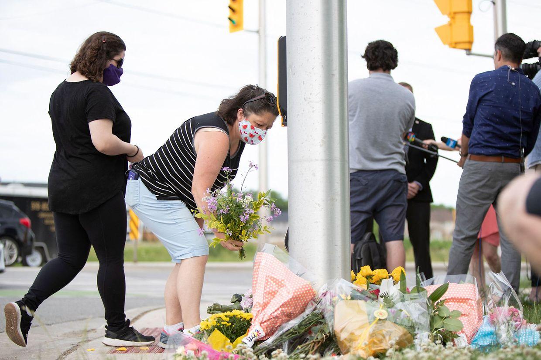 Menschen legen Blumen am Tatort nieder.