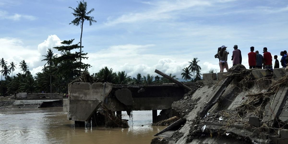 This photo taken on December 23, 2017 shows residents looking at the Cabuyao Bridge, which collapsed after being hit by Tropical Storm Tembin, in Barangay Dalama, Tubod, Lanao del Norte on the southern Philippine island of Mindanao.   Tens of thousands have been forced from their homes by a tropical storm that battered the southern Philippines leaving at least 182 dead, police and aid agencies said on December 24. / AFP PHOTO / MERLYN MANOS