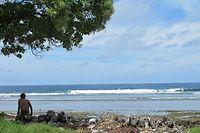 ARCHIV - 25.07.2012, Kiribati, Tarawa: Ein Junge sitzt am Sandstrand auf der Fidschi-Insel Kiribati neben Abfällen. Das Institute for Economics and Peace stellt eine Studie zu ökologischen Bedrohungen und Klimaflüchtlingen vor. Foto: Christiane Oelrich/dpa +++ dpa-Bildfunk +++