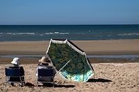 Sunbathers look out from chairs on the beach, in Houlgate, north-western France, on June 5, 2021. (Photo by JOEL SAGET / AFP)
