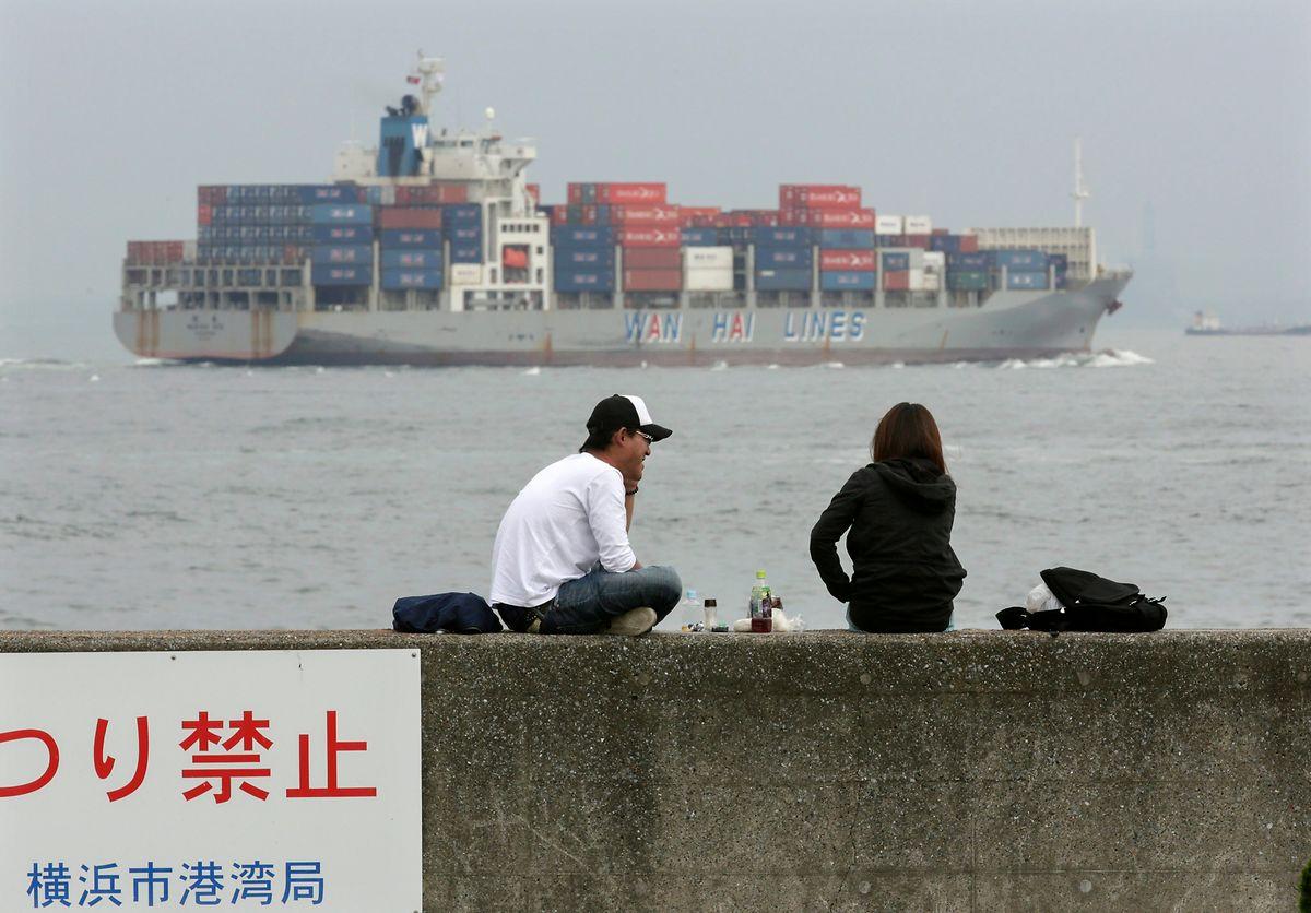 Yokohama: Ein Paar macht eine Mittagspause, während im Hintergrund ein Containerschiff durch die Tokio-Bucht fährt.