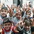 Syrian refugee children make the V-sign for victory as they pose for the camera in the Zaatari refugee camp, a seven-square-kilometre (2.8-square-mile) camp that is home to more than 100,000 refugees, on April 15, 2014, some 10 days after riots killed one refugee and left dozens, mainly policemen, injured. The kingdom which neighbours Syria along its northern borders is hosting more than 500,000 Syrian refugees. AFP PHOTO/KHALIL MAZRAAWI