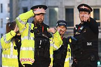 Police gesture to members of the public as they clear the area  near London Bridge in London, on November 29, 2019 after reports of shots being fired on London Bridge. - A man wearing a suspected hoax explosive device was shot dead by armed officers on London Bridge on Friday after a stabbing spree, in what police said was a terrorist incident. (Photo by DANIEL SORABJI / AFP)