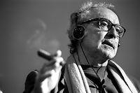 """ARCHIV - 08.02.2002, Schweiz, Zürich: Der Filmregisseur Jean-Luc Godard mit Kopfhöhrern und Zigarre während eines Filmvortrags an der ETH Zürich. Der Altmeister Godard wird am 3. Dezember 2020 90 Jahre alt. (Zu dpa: """"Altmeister Godard wird 90: Der Bilderstürmer des französischen Kinos"""") Foto: Christof Schuerpf/epa/dpa +++ dpa-Bildfunk +++"""