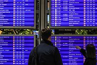 Passengers check their flights at a departure information board at Frankfurt International Airport in Frankfurt am Main, western Germany, on December 21, 2020, amid the ongoing novel coronavirus / COVID-19 pandemic. - Germany and countries around the world have begun banning flights and travellers from the UK after a new strain of coronavirus was detected there. (Photo by Armando BABANI / AFP)