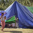 An Indonesian woman carrying a baby walks past tents at a temporary shelter for earthquake-affected residents in Pemenang, West Nusa Tenggara on August 14, 2018. - The death toll from an earthquake on the Indonesian island of Lombok has topped 400, authorities said, as bodies were still being recovered from the ruins of destroyed buildings. (Photo by STR / AFP)