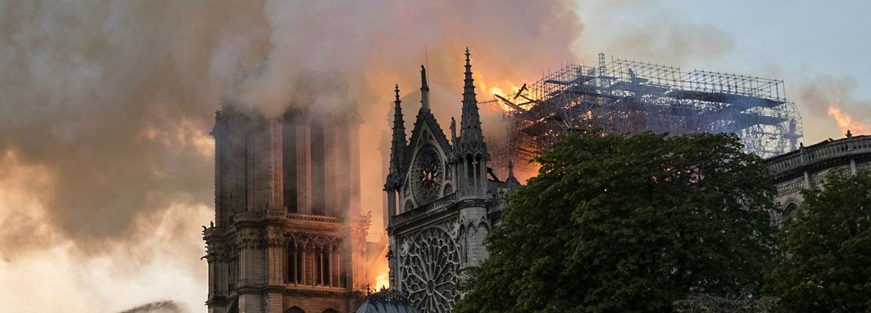 "A firefighter uses a hose to douse flames billowing from the roof at Notre-Dame Cathedral in Paris on April 15, 2019. - Pope Francis stands with France and is praying for Roman Catholics and Parisians alike after a devastating fire raged through the iconic Notre-Dame cathedral in the heart of the city,"" the Vatican said on April 16. (Photo by THOMAS SAMSON / AFP)"