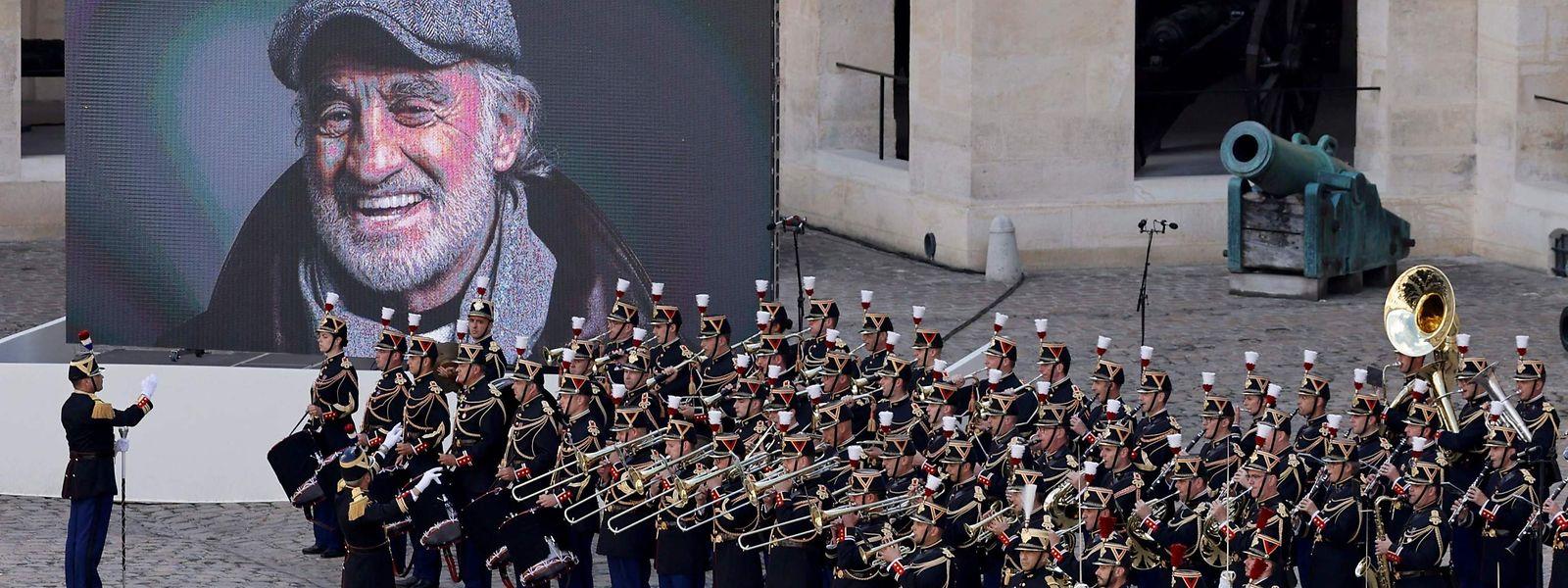 Ein schon weißhaariger Jean-Paul Belmondo, der aus der Ecke des Ehrenhofs im Pariser Invalidendom auf die rund tausend Trauergäste lächelt.