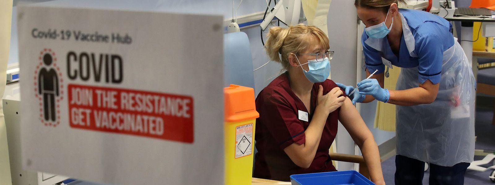 Krankenpflegerin impft Krankenpflegerin: Während Luxemburgs Abgeordnete die Impfstrategie debattieren, startete am Dienstag in Großbritannien die größte Impfaktion, die das Land je erlebte.