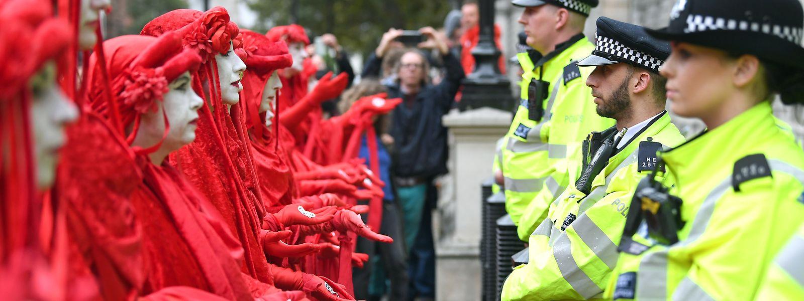 Aktivisten der Klimabewegung «Extinction Rebellion» stehen in roten Gewändern gegenüber von Polizisten vor dem Cabinet Office in London.