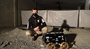 Space systems engineer Federico Giusto of iSpace Europe poses with a model of a moon rover being tested in Luxembourg.
