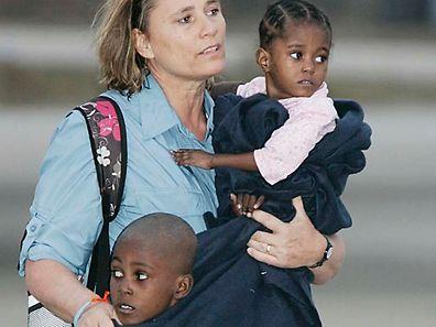 Mitarbeiter der Adoptionsagenturen und Krankenschwestern tragen die Kinder vom Flugzeug zu den wartenden Bussen.
