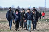 Migrants walk away from the Turkey-Greece border buffer zone near Pazarkule crossing gate in Edirne, on March 7, 2020, during clashes between Greek police and migrants trying to cross to the Greek side. - Greece plans to build two new temporary camps to house hundreds of additional asylum seekers who arrived after a surge enabled by Turkey, the migration minister said Saturday. (Photo by Ozan KOSE / AFP)