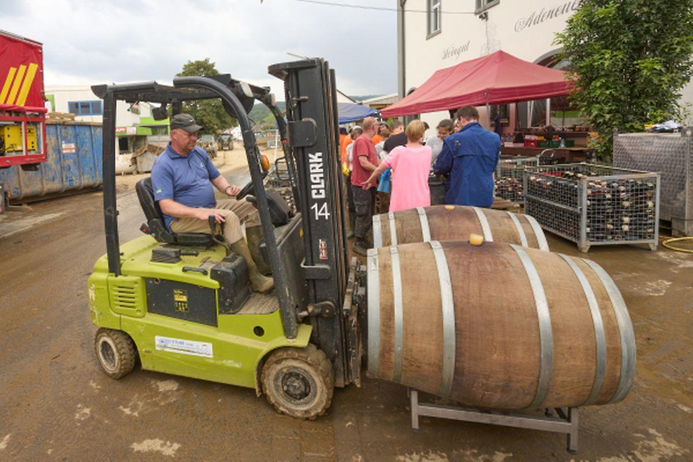 27.07.2021, Rheinland-Pfalz, Ahrweiler: Freiwillige Helfer sind am Weingut Adeneuer damit beschäftigt, die durch die Flut mit Schlamm bedeckten Flaschen zu reinigen. Im durch das Hochwasser stark verwüsteten Ahrtal gehen die Aufräumarbeiten unvermindert weiter. Foto: Thomas Frey/dpa +++ dpa-Bildfunk +++