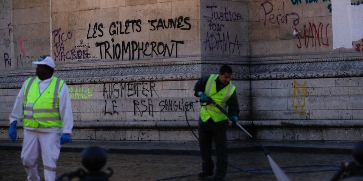 "Workers clean around the ""Arc de Triomphe"" a day after a Yellow vests (Gilets jaunes) demonstration against rising oil prices and living costs, on December 2, 2018 in Paris. A grffiti on the monument reads ""yellow vests will triumph"". - Anti-government protesters torched dozens of cars and set fire to storefronts during daylong clashes with riot police across central Paris yesterday, as thousands took part in fresh ""yellow vest"" protests against high fuel taxes. (Photo by Geoffroy VAN DER HASSELT / AFP)"