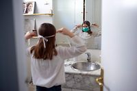 Ines, 11, puts on her face mask prior to going out with her family on April 26, 2020, in Barcelona, during a national lockdown to prevent the spread of the COVID-19 disease. - After six weeks stuck at home, Spain's children were being allowed out today to run, play or go for a walk as the government eased one of the world's toughest coronavirus lockdowns. Spain is one of the hardest hit countries, with a death toll running a more than 23,000 to put it behind only the United States and Italy despite stringent restrictions imposed from March 14, including keeping all children indoors. Today, with their scooters, tricycles or in prams, the children accompanied by their parents came out onto largely deserted streets. (Photo by Josep LAGO / AFP)
