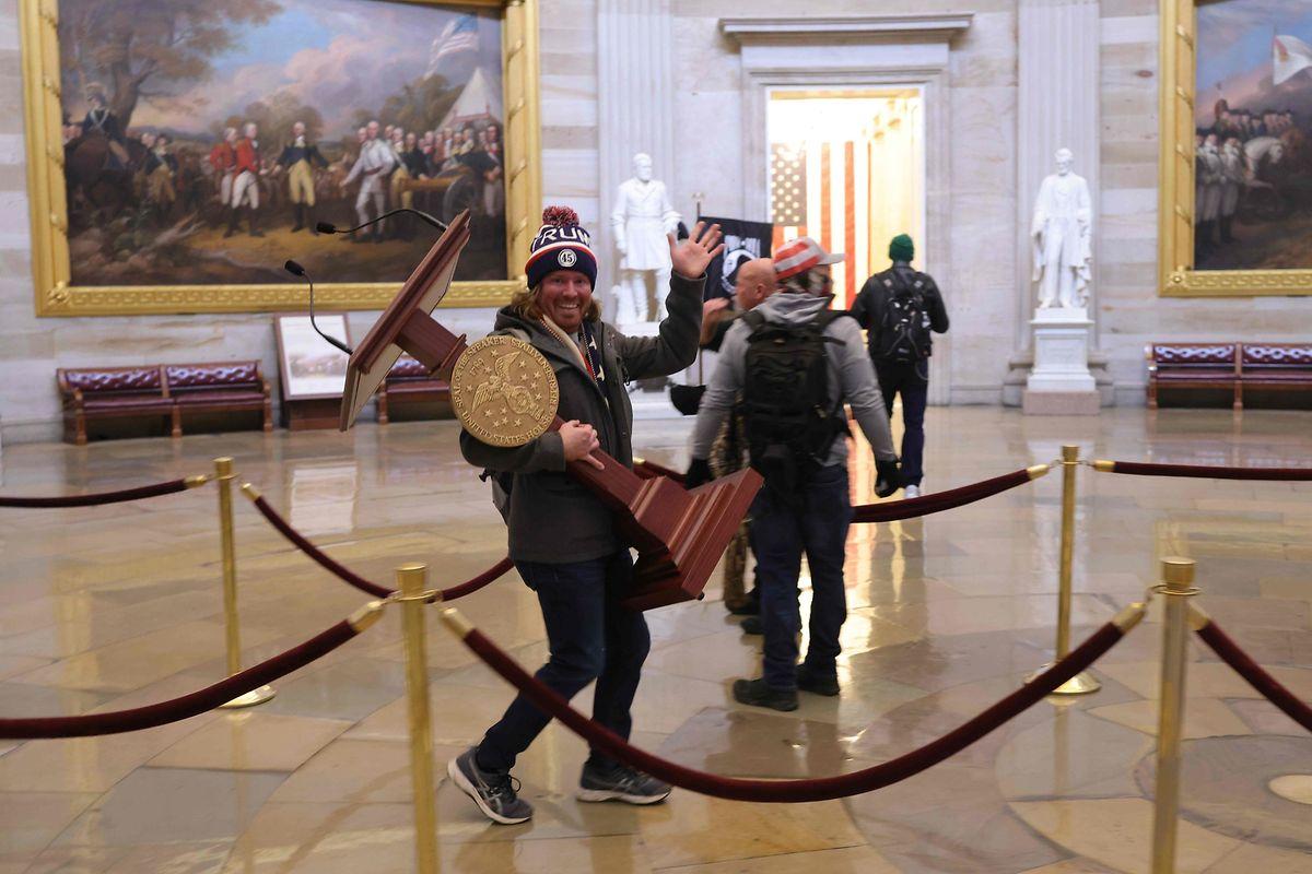 Ein Trump-Anhänger stiehlt ein Rednerpult aus dem US-Kapitol.