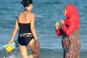 "(FILES) This file photo taken on August 16, 2016 shows Tunisian women, one (R) wearing a ""burkini"", a full-body swimsuit designed for Muslim women, walking in the water at Ghar El Melh beach near Bizerte, north-east of the capital Tunis.  The debate launched this summer in France over the Burkini is not causing such a stir in North Africa where the Islamic swimsuit is uncontroversial as the dress-code on the beaches has become increasingly prudish.  / AFP PHOTO / FETHI BELAID / TO GO WITH AFP STORY BY AMAL BELLALOUFI WITH AFP CORRESPONDENTS IN RABAT AND TUNIS"