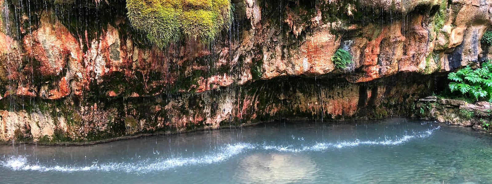 An dem mit Moos bewachsenen Felsvorsprung fließt glasklares, kalkhaltiges Wasser in das türkisfarben schimmernde Becken.
