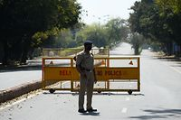 """A policeman stands guard at a road checkpoint the day after Indian Prime Minister Narendra Modi announced a 21-day government-imposed nationwide lockdown as a preventive measure against the COVID-19 coronavirus in New Delhi on March 25, 2020. - India's 1.3 billion people will go under """"total lockdown"""" from midnight on March 24 (1830 GMT) for 21 days to combat the spread of the coronavirus pandemic, Prime Minister Narendra Modi said. (Photo by Sajjad HUSSAIN / AFP)"""