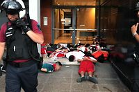 """TOPSHOT - Video grab showing security forces arresting guarding detained supporters of River Plate during clashes in the surroundings of the Monumental stadium in Buenos Aires following an attack on the Boca team bus before the all-Argentine Copa Libertadores second leg final match between River Plate and Boca Juniors on November 24, 2018. - Saturday's """"superclasico"""" Copa Libertadores final was postponed until Sunday following an attack on the Boca team bus that left players affected by smoke inhalation and broken glass. (Photo by Ivan PISARENKO / AFP)"""