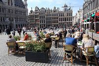 People sit at cafes' terraces at Brussels' Grand place on the second day of the reopening of the country's terraces in Brussels, on May 9, 2021, as part of the easing of the country's second lockdown aimed at curbing the spread of the Covid-19 pandemic, . (Photo by Fran�ois WALSCHAERTS / AFP)