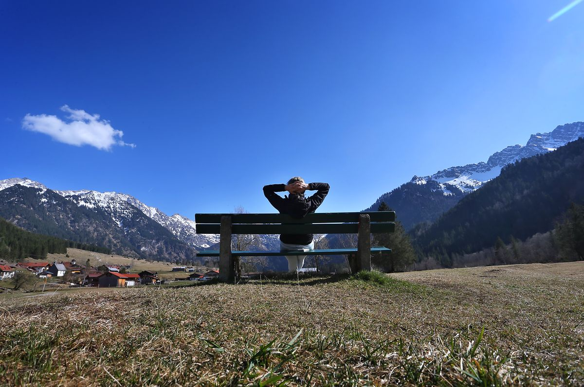 Bayern, Bad Hindelang: Eine Wanderin genießt auf einer Bank im Hintersteiner Tal den Sonnenschein und die Aussicht auf das Panorama der Berge.