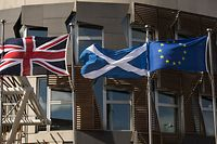 (FILES) This file photo taken on June 27, 2016 shows a Scottish Saltire (C) flies between a Union flag (L) and a European Union (EU) flag in front of the Scottish Parliament building in Edinburgh, Scotland on June 27, 2016. The Scottish parliament is expected to officially register its opposition to the British government's march towards Brexit on February 7, 2017 in a vote that will further strain the bonds of the United Kingdom. Scotland's nationalist government has said the vote will be one of the most significant in the devolved parliament's 18-year history.  / AFP PHOTO / OLI SCARFF