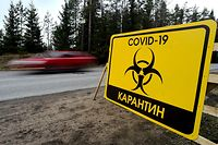 "A sign reading ""Quarantine COVID-19"" is pictured at the entrance to the village of Pervomaiskoye outside Saint Petersburg on May 3, 2020 amid the coronavirus pandemic. - Entry into the settlement has been prohibited since April 30 as the rate of virus infection is 2.5 times higher than in Leningrad region. (Photo by Olga MALTSEVA / AFP)"