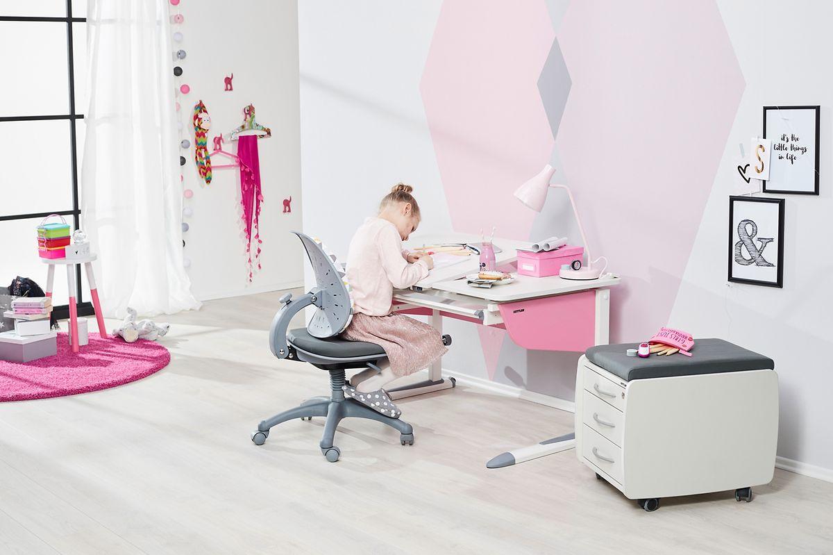 Auf einer zweigeteilten Tischplatte lässt sich ein Teil anheben für etwa das Schreiben und Malen und der andere bleibt als Ablage gerade.