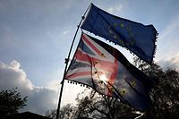 """Anti-Brexit activists fly EU and Union flags as they demonstrate near the Houses of Parliament in central London on April 3, 2019. - Prime Minister Theresa May met Wednesday with Britain's opposition leader in a bid to forge a Brexit compromise that avoids a potentially chaotic """"no-deal"""" departure from the EU in nine days. May tore up her steadfast strategy and sought Labour leader Jeremy Corbyn's support in a surprise last-minute move that could determine the fate of the country and her government. (Photo by ISABEL INFANTES / AFP)"""