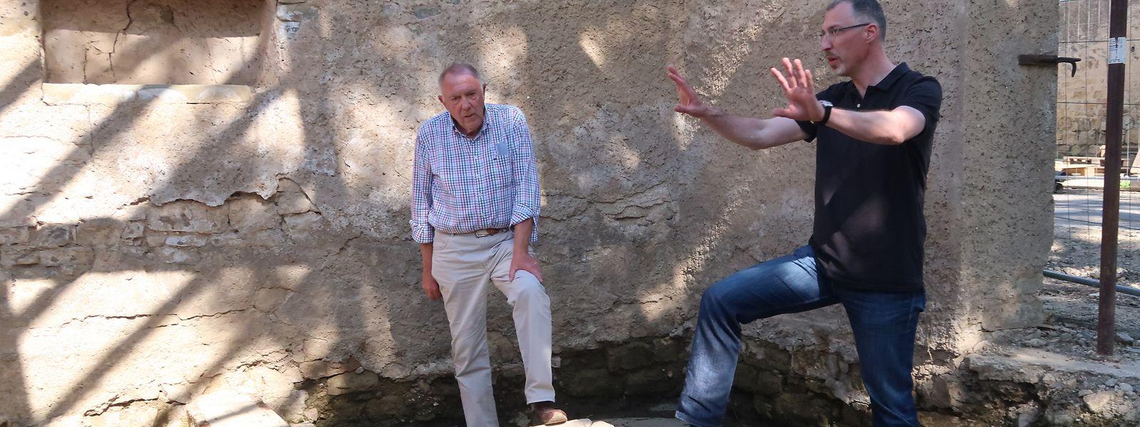 Lokalhistoriker Paul Weber (links) und Bürgermeister Jean-François Wirtz besichtigen den unerwarteten Fund. Sogar die Wasserleitung ist noch erhalten.