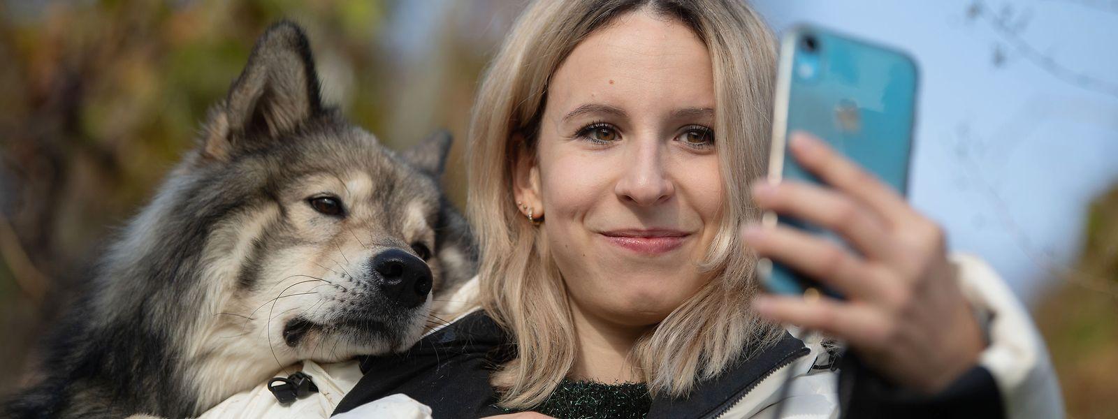 Nicole Lenhardt macht mit ihrem Wolfshund Milo in einem Weinberg ein Selfie. Mit Hilfe ihres Haustiers ist die Stuttgarterin über Internet-Plattformen so erfolgreich geworden, dass sie vor kurzem ihren Job aufgegeben und sich selbstständig gemacht hat.