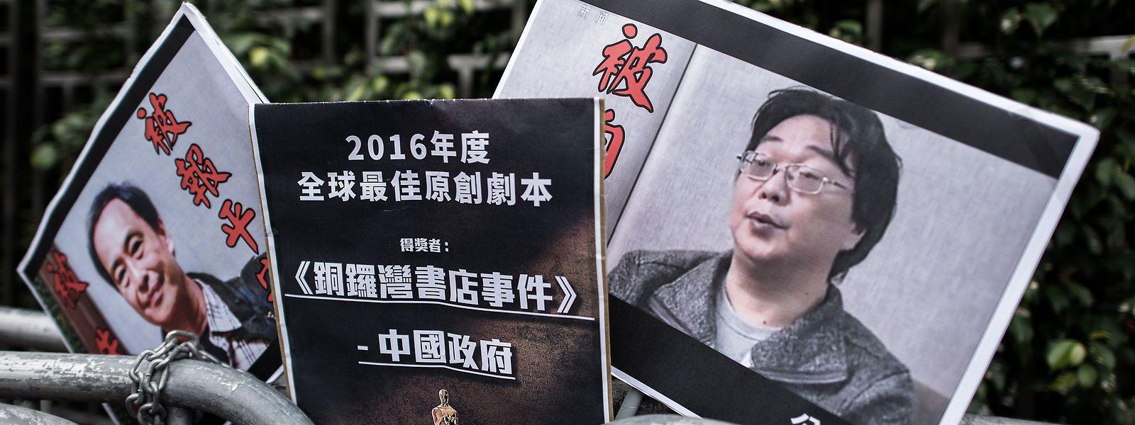 Die Protestplakate zeigen die im Jahr 2015 verschwundenen Verleger Lee Bo (l.) und Gui Minhai (r.). Gui wurde am Dienstag zu zehn Jahren Haft verurteilt.